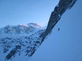 Traversing above the bergschrund with the Isis Face and Denali in the morning alpenglow.